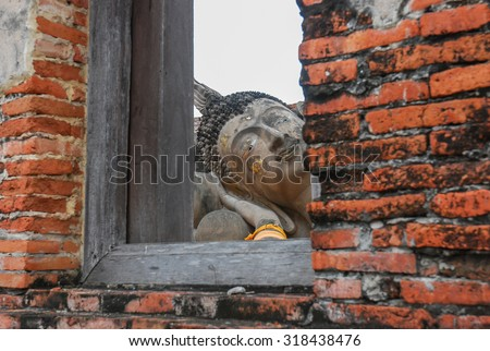 Ruin and ancient orange brick wall with a window view to the trees of Ayuttaya province in Thailand. - stock photo