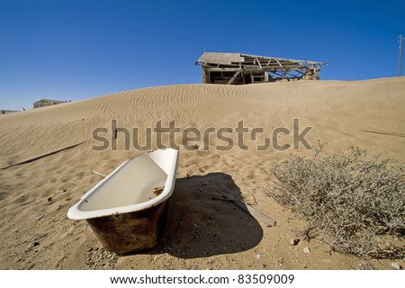 Ruin of an abandoned house and artifacts in the ghost diamond town Kolmanskop near Lüderitz, Namibia, Africa - stock photo
