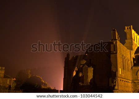 ruin of Melrose Abbey illuminated at night - stock photo