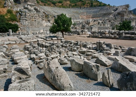 Ruined city of Ephesus in Turkey, founded on 10th century BC.  Greek theater on the background and archeology artifacts around. - stock photo