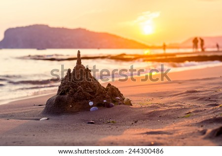 Ruined sandcastle on the beach at sunset in Alanya, Turkey - stock photo
