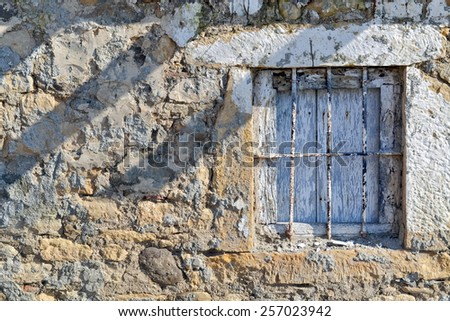 Ruined stone wall and window of an old abandoned house - stock photo