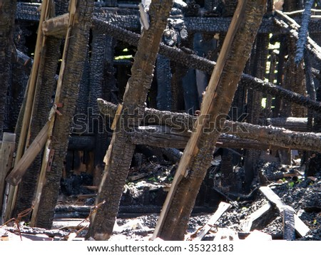 Ruined wood log house burnt by fire to black coal