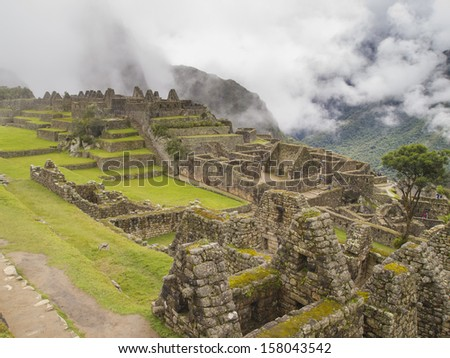 Ruins Buildings in Machu Picchu - Mysterious city and archaeological site of pre-Columbian civilization of the Incas on the Andes cordillera mountains archeology near Cusco, Peru. - stock photo