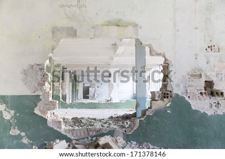 Ruins of a huge empty building seem from a hole in the wall - stock photo