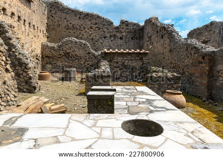 Ruins of an ancient bar (thermopolium) in Pompeii, Italy. Pompeii is an ancient Roman city died from the eruption of Mount Vesuvius in 79 AD. - stock photo