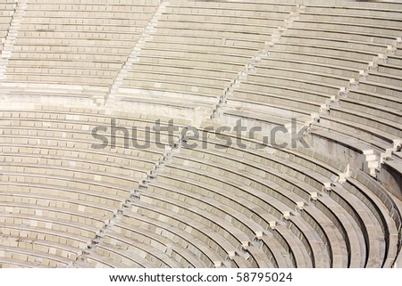 Ruins of an ancient greek Amphitheater in Athens, rows of seats and steppes - stock photo
