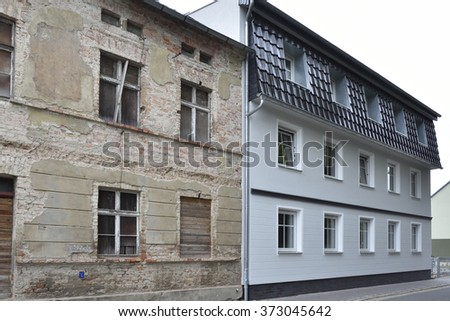 Ruins of an old house next to a new house - stock photo