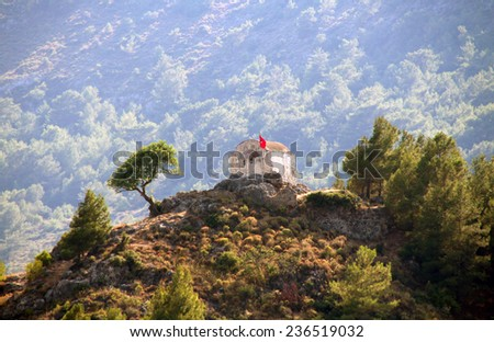 Ruins of ancient church on top of the hill in ghost town of Kayakoy (Turkey) - stock photo