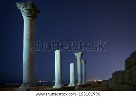 Ruins of ancient city columns under blue night sky with moon and stars - stock photo