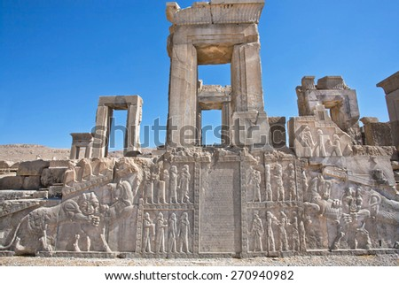 Ruins of ancient palace with columns and bas-relief with symbols of Zoroastrians - fighting bull and a lion, Persepolis, modern Iran. Persepolis was a capital of the Achaemenid Empire (550 - 330 BC)   - stock photo