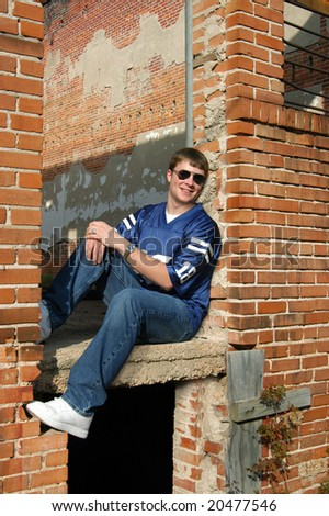 Ruins of brick building is resting place for male teen.  He has on a blue jersey style shirt and sunglasses.