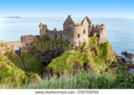 Ruins of medieval Dunluce Castle, County Antrim, Northern Ireland, at sunrise light  - stock photo
