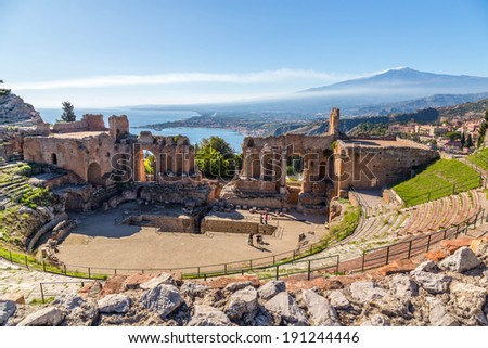 Ruins of the ancient greek theater of Taormina, Sicily the Etna with its double snook tail in the background above the morning sun lit Giardini-Naxos bay of the Ionian see. - stock photo