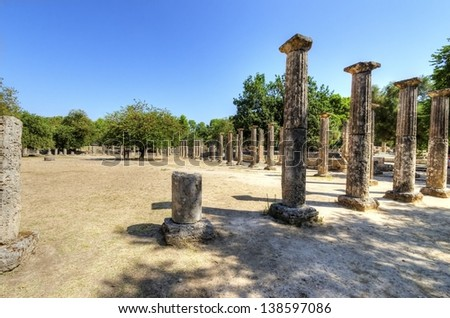 Ruins of the ancient site of Olympia, in Greece, where the Olympic games originate from. A number of lined up columns, which used to be the Palestra. - stock photo