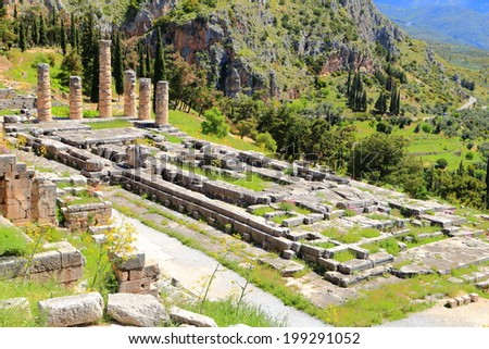 Ruins of the Apollo temple at Delphi surrounded by wild flowers in the spring, Greece  - stock photo