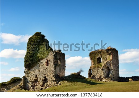 Ruins of the ivy clad Gleaston Castle, a 14th century fortification situated near Ulverston, Cumbria, set against a glorious blue sky with cumulus clouds - stock photo