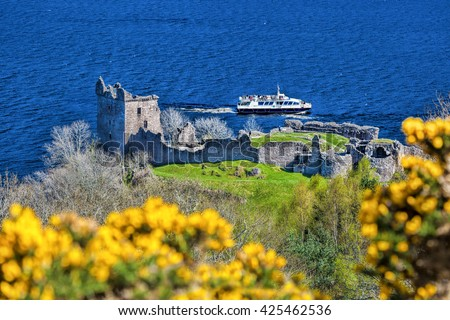 Ruins of Urquhart Castle against boat on Loch Ness in Scotland - stock photo