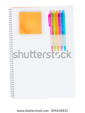 Ruled notebook with set of pens and orange sticker isolated on white background - stock photo