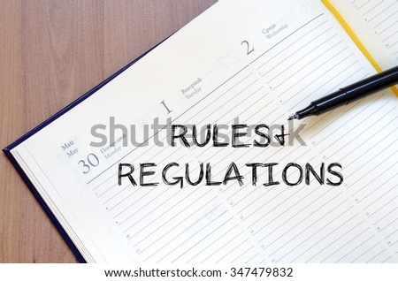 Rules and regulations text concept write on notebook with pen