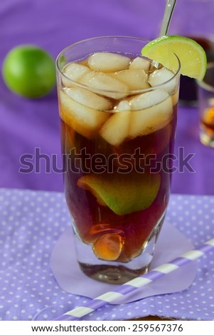 Rum and Coke Cocktail Drink with Lime Wedges and Ice Cubes - stock photo