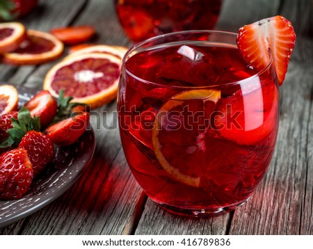 Rum punch with blood orange and strawberries on a wooden table