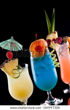 Rum Runner, Bahama Mama, and Blue Lagoon cocktails over black background on reflection surface, garnished with pineapple flag, fresh raspberry, maraschino cherry, and lime twist.   - stock photo