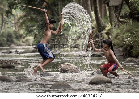 Rumpin, Bogor, Indonesia - April 16, 2017 : Boys playing a traditional martial art from Lombok (Peresean) in the river