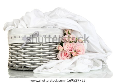 Rumpled bedding sheets in wicker basket isolated on white - stock photo