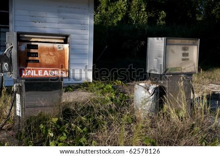 Run down gas pumps at an abandoned petrol station. - stock photo