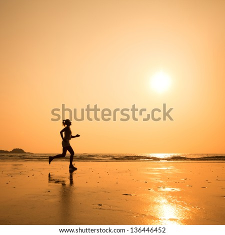 run to purpose, woman silhouette on the beach - stock photo