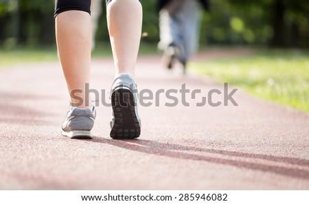 Runner athlete feet running on road  - stock photo
