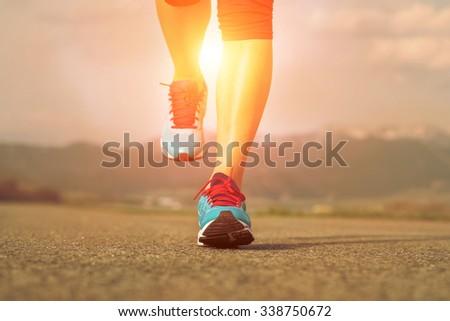 Runner athlete feet running on road under sunlight. - stock photo