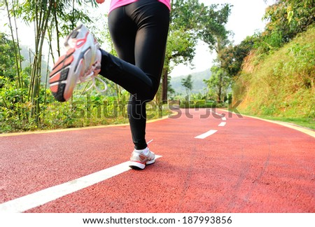 runner athlete feet running on road. woman fitness jogging workout wellness concept