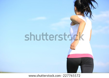 Runner athlete running against blue sky. woman fitness jogging workout wellness concept.  - stock photo