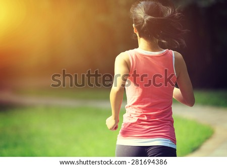 Runner athlete running at park trail. woman fitness jogging workout wellness concept.  - stock photo