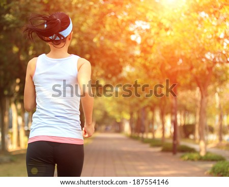 Runner athlete running at park woman fitness jogging workout wellness concept.   - stock photo