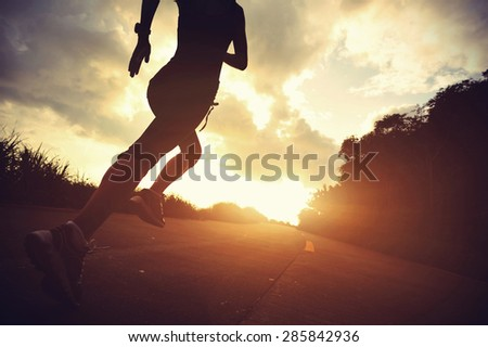 Runner athlete running at seaside road. woman fitness silhouette sunrise jogging workout wellness concept. - stock photo