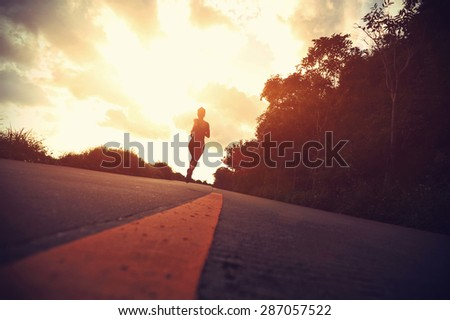 Runner athlete running at seaside road. woman fitness silhouette sunrise jogging workout wellness concept.