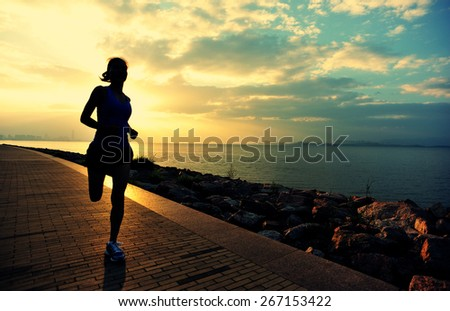 Runner athlete running at seaside. woman fitness silhouette sunrise jogging workout wellness concept.