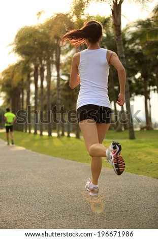 Runner athlete running at sunrise tropical park. woman fitness sunrise jogging workout wellness concept.  - stock photo
