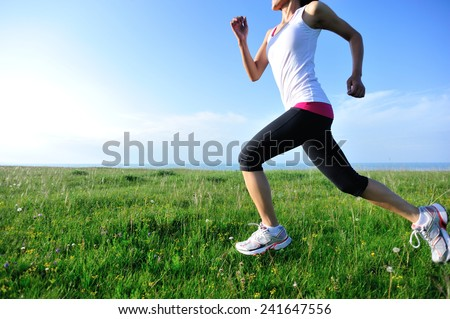 Runner athlete running on grass seaside. woman fitness jogging workout wellness concept.  - stock photo