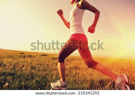 Runner athlete running on grass seaside. woman fitness sunrise/sunset jogging workout wellness concept.  - stock photo