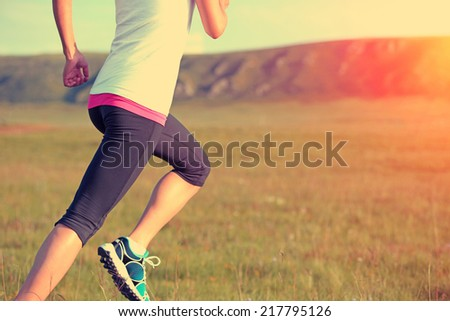 Runner athlete running on grass seaside. woman fitness sunrise/sunset jogging workout wellness concept.  - stock photo