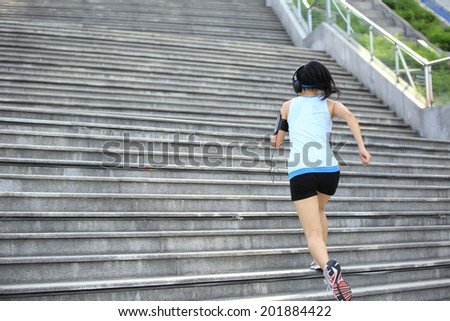 Runner athlete running on stairs. listening to music in headphones from smart phone mp3 player smart phone armband.woman fitness jogging workout wellness concept.