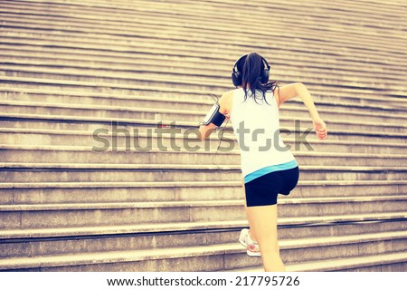 Runner athlete running on stairs. listening to music in headphones from smart phone mp3 player woman fitness jogging workout wellness concept.  - stock photo