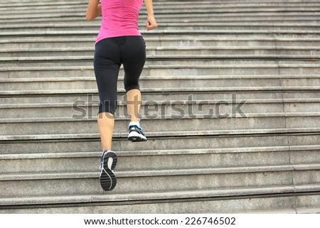 Runner athlete running on stairs. woman fitness jogging workout wellness concept.