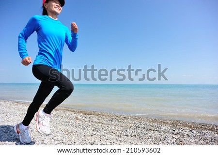 Runner athlete running on stone beach of qinghai lake. woman fitness jogging workout wellness concept.