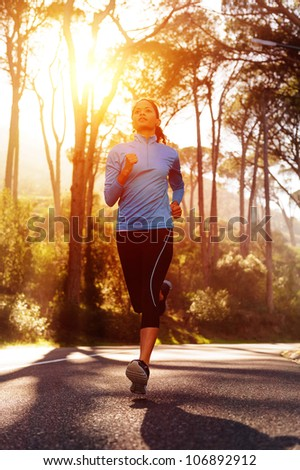 Runner athlete training running on road. woman fitness sun flare sunrise jog workout wellness concept. - stock photo