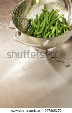Runner beans in strainer on kitchen table - stock photo